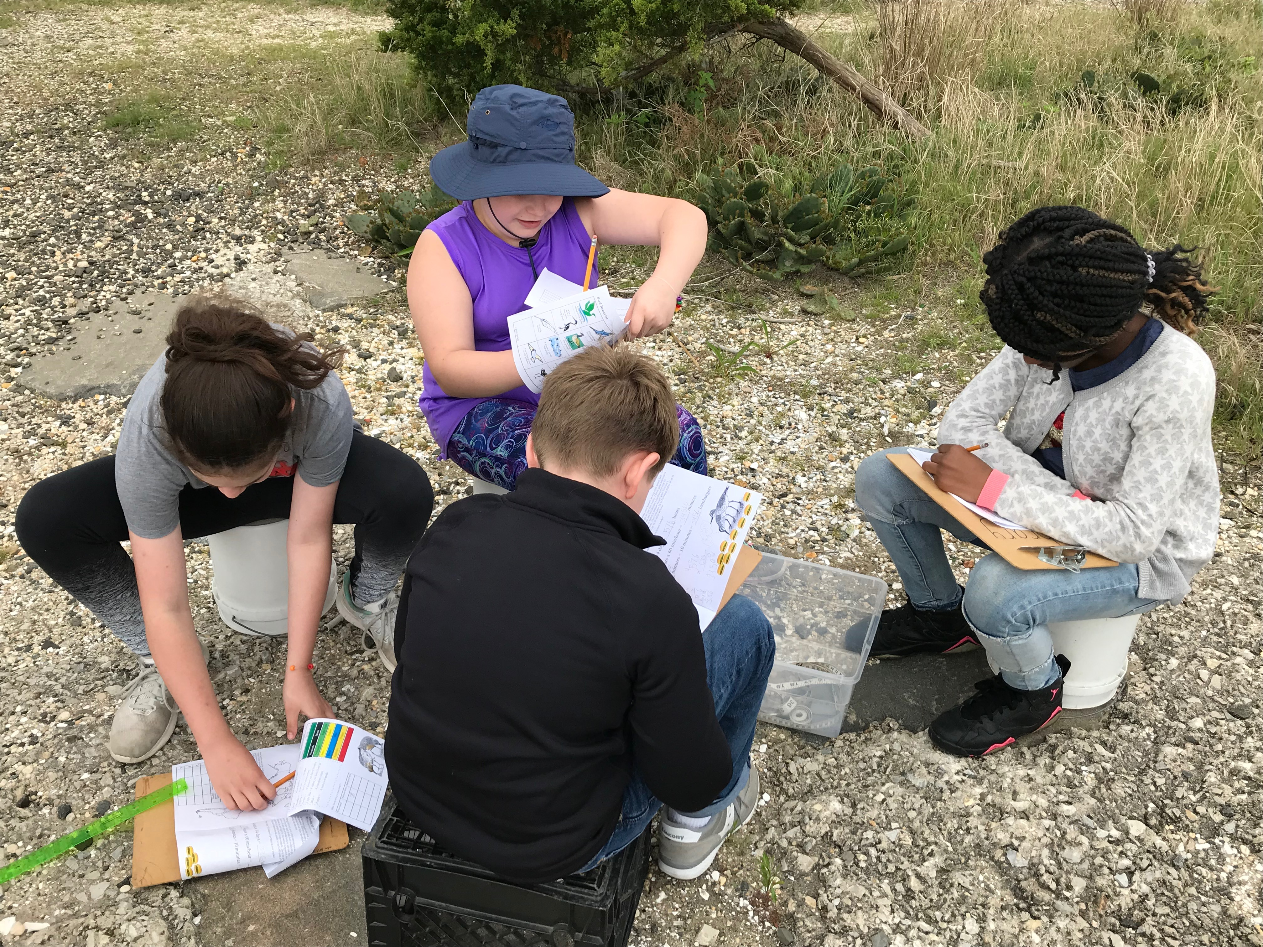 students take scientific measurements outdoors